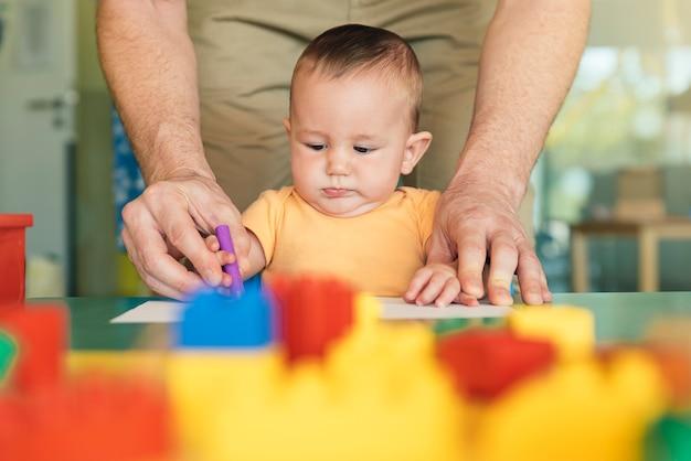 어린 아이와 아버지가 종이에 그림을 그리고 있습니다. 유치원 개념입니다.