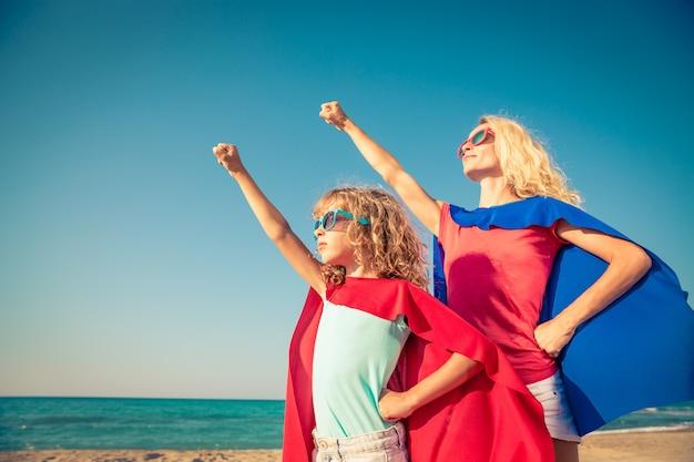 Маленький ребенок и ее мама, одетые как супергерой, поднимают руки на пляже