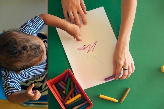 어린 아이와 엄마가 종이에 그림을 그리고 있습니다. 유치원 개념입니다.