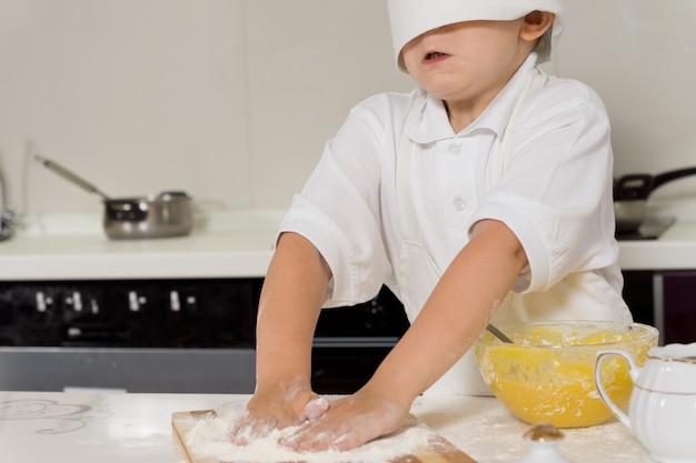 Little child baking in a chefs toque