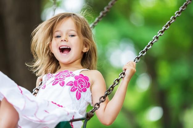 ブランコで楽しんでいる小さな子供ブロンドの女の子