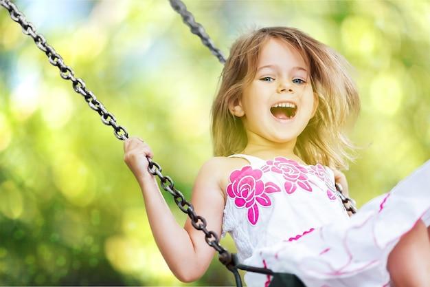Little child blond girl having fun on a swing