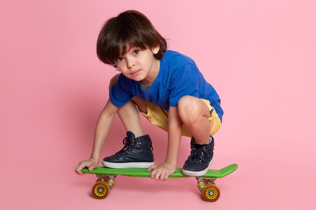 Little child boy in blue t-shirt riding on skateboard on pink wall
