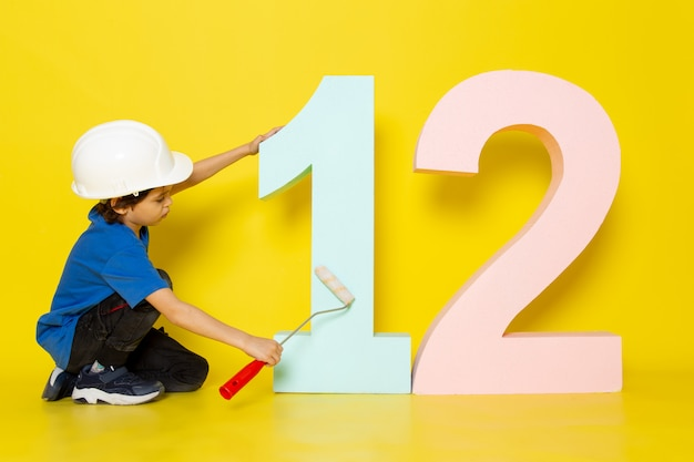 Little child boy in blue t-shirt and white helmet touching number figure on yellow wall