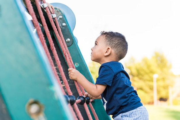 Little child boy climbing a rope in the park.