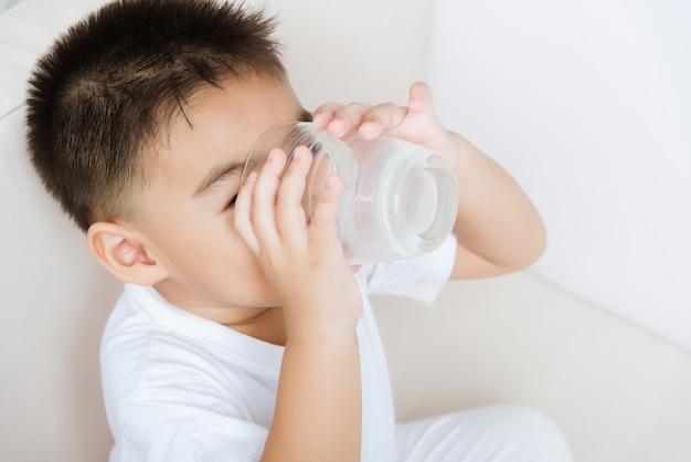 Маленький ребенок мальчик рука держит стакан молока, он пьет белое молоко