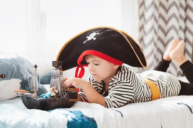 海賊の帽子とカーニバルの衣装を着た小さな子供男の子が子供部屋で海賊船のおもちゃで遊んでいます。