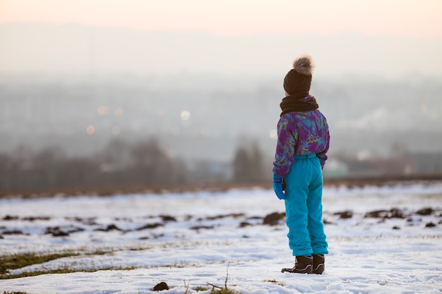 Little child boy standing outdoors alone on snow covered winter field.