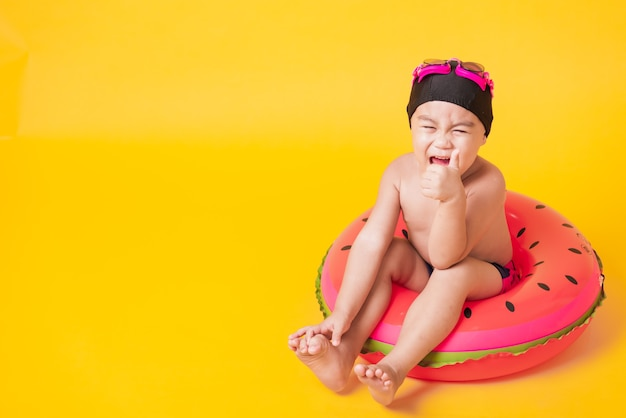 Little child boy wear goggles in swimsuit on watermelon inflatable ring