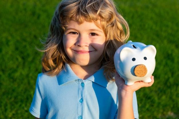Little child boy with piggy bank outdoor kid hold saving piggybank