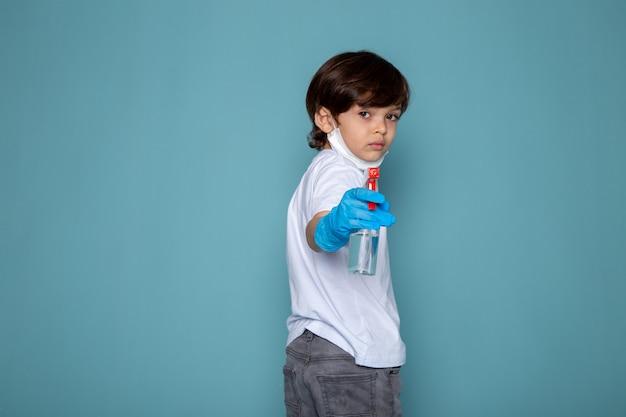 파란색 책상에 파란색 장갑에 코로나 바이러스에 대한 그의 손에 스프레이와 작은 아이 소년