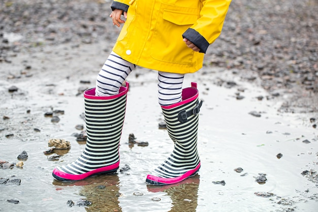 Little child in a bright yellow raincoat and striped rubber boots.
