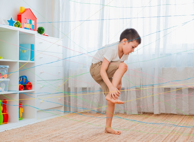 Little child climbing through a rope web