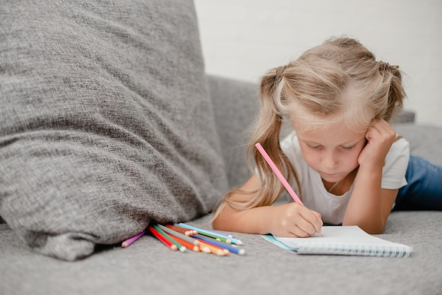 Little child drawing lying on thesofa in the living-room.