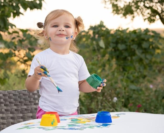 Маленький детский рисунок с краской и кистью. милая маленькая девочка рисует картину в саду, на открытом воздухе у себя дома на заднем дворе