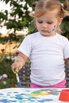 Little child drawing with paint and brush. cute small girl painting picture in garden, outdoors at home in backyard
