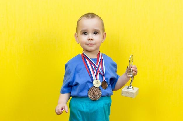 Маленький ребенок мечтает о спортивной победе, желтый фон.