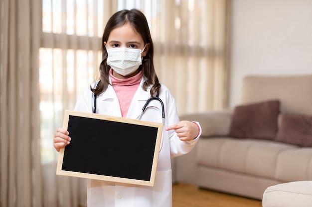 医者に扮した小さな子供が、黒板を手で持って指さしている医療用マスクを着用しています。