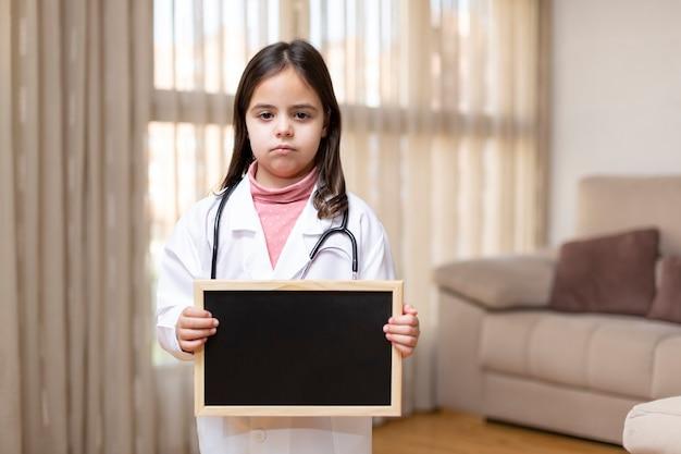 医者に扮した小さな子供が、家で黒板を持って真剣なジェスチャーをしている