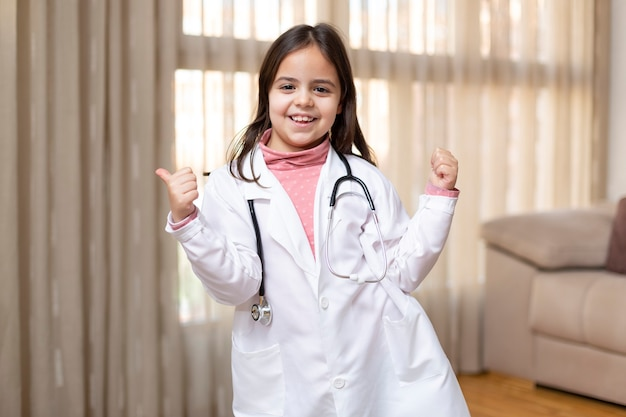 医者の制服を着た小さな子供が楽しく前向きな態度で親指をあきらめる