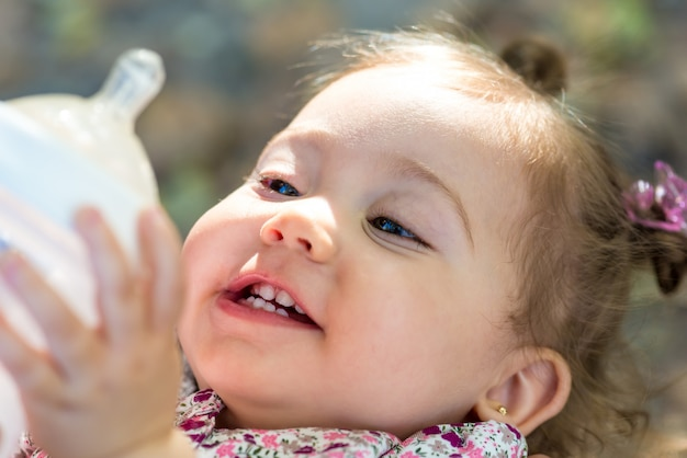 Little child drinking milk from baby bottle outdoors.