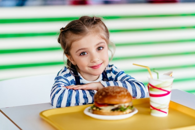 Маленький ребенок ест гамбургер в кафе