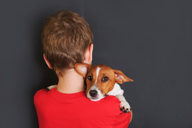 Little child embracing cute puppy jack russell.