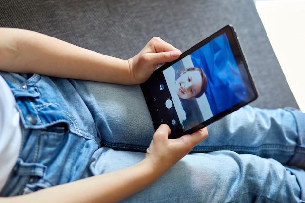 집에서 어린 아이 소녀는 태블릿 회의, 온라인 통화 친구와 비디오 이야기
