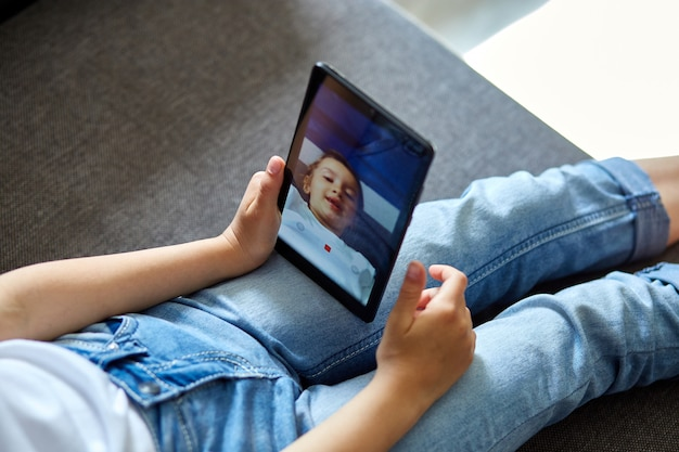 自宅で小さな子供女の子がタブレット会議、オンライン通話の友人とビデオを話す Premium写真