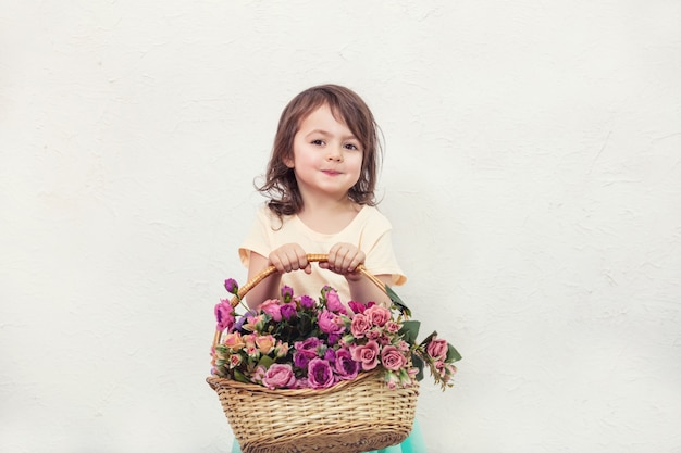 小さな子供の女の子は、白い壁の背景に花で美しく、かわいいと幸せ
