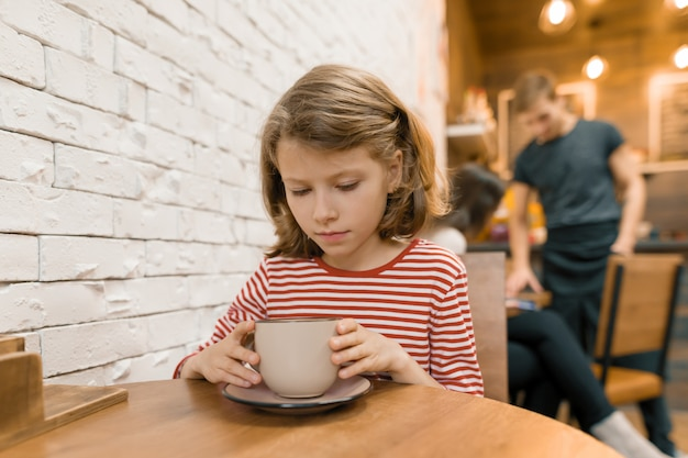 Little child girl in cafe with big cup of art drink