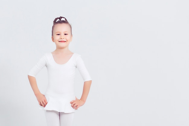Маленькая девочка танцует балет на белом фоне портрет маленькой балерины улыбается