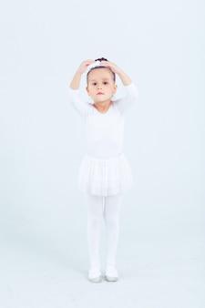 Little child girl dance ballet at white background portrait of small ballerina smiling