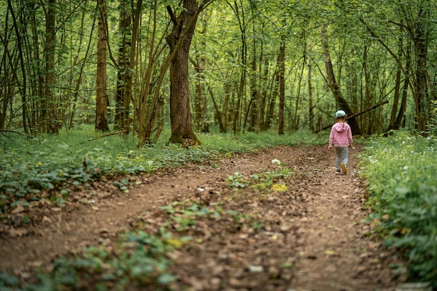 Little child girl in dense forest walks along trail into depths forest.