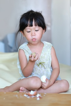 Little child girl eating boiled eggs at home.