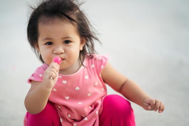 小さな子供の女の子がロリポップキャンディーを食べてお楽しみください。