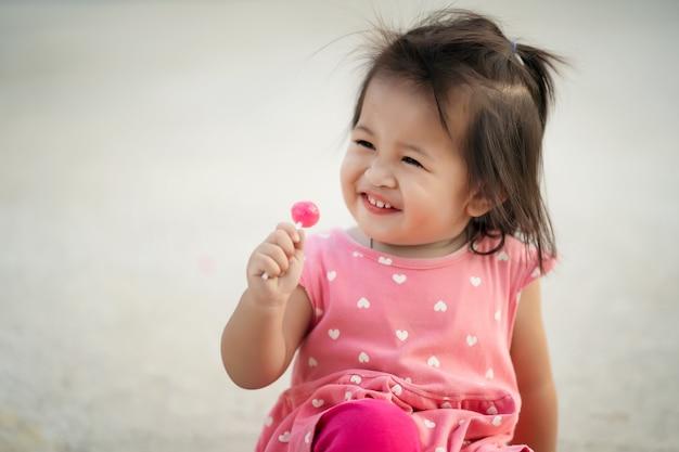 Little child girl enjoy eating lollipop candy
