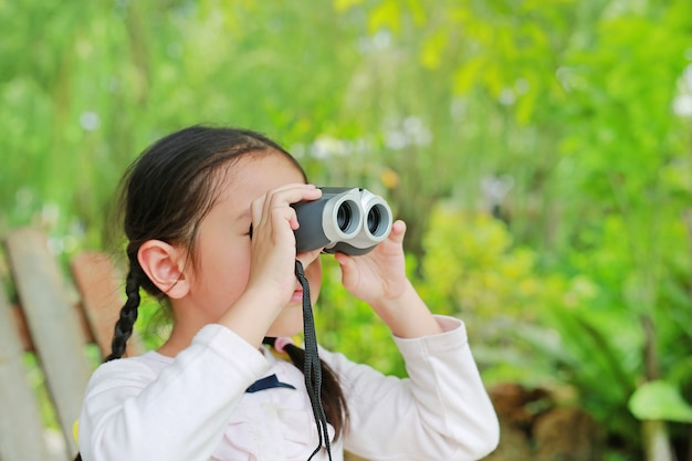 Little child girl in a field looking through binoculars in nature outdoor.