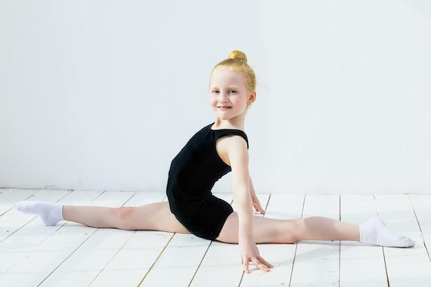 Маленькая детская гимнастка делает растяжку в яркой комнате на счастливой и милой