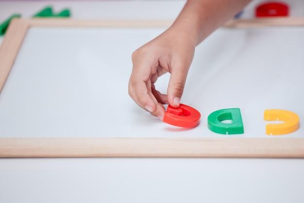 小さな子供の女の子の手を再生し、ボード上の磁気アルファベットを学ぶ