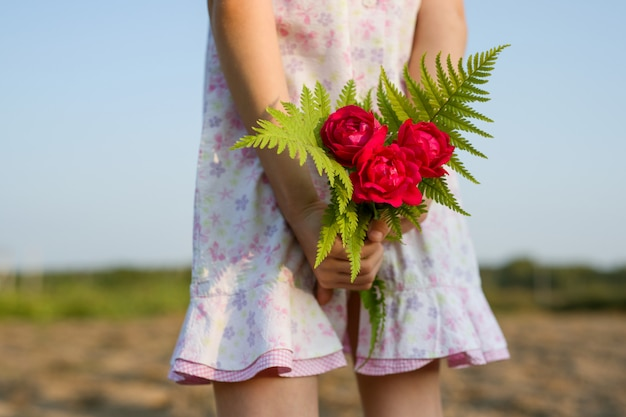 Little child girl holding bouquet of flowers.