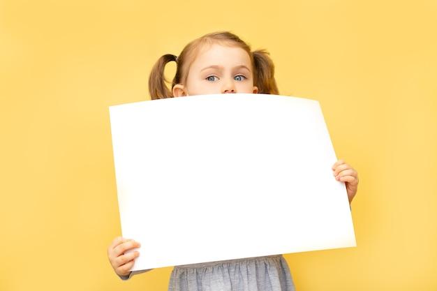 노란색 벽에 종이의 빈 시트를 들고 어린 아이 소녀. 텍스트 공간 장소 복사