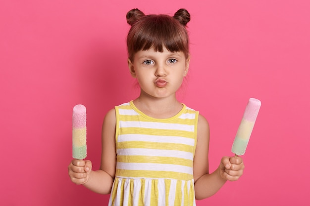 Little child girl holding ice creams in both hands,  with rounded lips, female child with two hair buns isolated over rose wall.