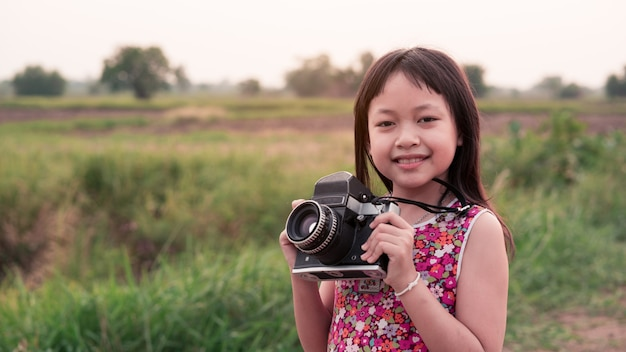 Little child girl holding medium format film camera and taking photo of sunset landscape with green field background