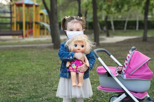 Маленькая девочка обнимает куклу в маске для защиты от вируса короны и загрязнения воздуха