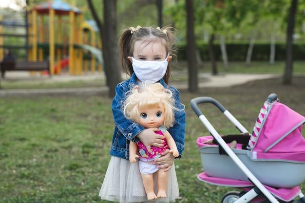 코로나 바이러스와 대기 오염 pm2.5에 마스크를 쓰고 인형을 껴안고 있는 어린 소녀
