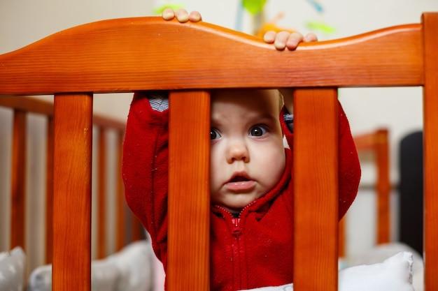 빨간 스웨터를 입은 어린 소녀, 아름답게 미소 짓고, 유아용 침대에서, 놀고, 재미있고 감정적인 사진을 가지고 있습니다