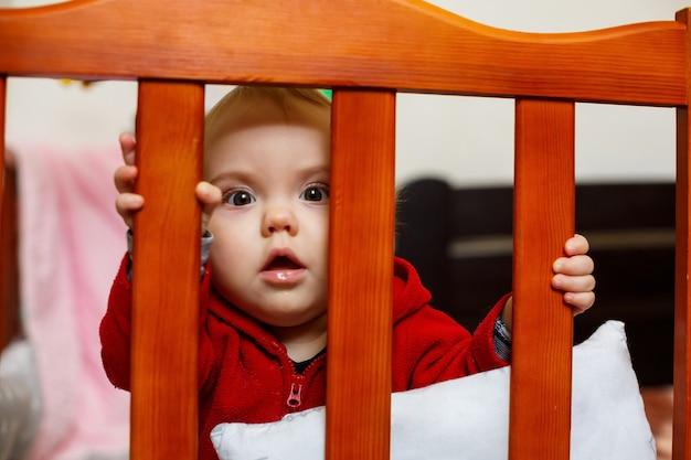 Маленькая девочка в красном свитере, красиво улыбается, в кроватке, играет и веселится, эмоциональное фото