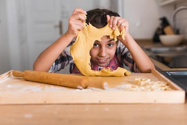 Маленькая девочка на кухне, одетая в фартук и шарф, как шеф-повар. девушка раскатывает тесто скалкой, улыбается счастливым. понятие: питание, кулинарная школа, образование.