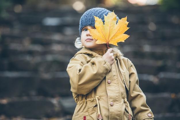 공원에서 가을 따뜻한 재킷과 모자에 어린 아이 소녀